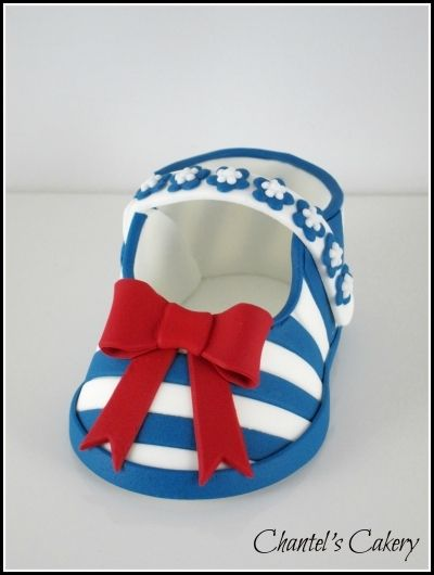 fondant baby shoe with blue stripes and red bow