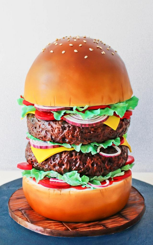 a tall burger cake with patties made of cake in it