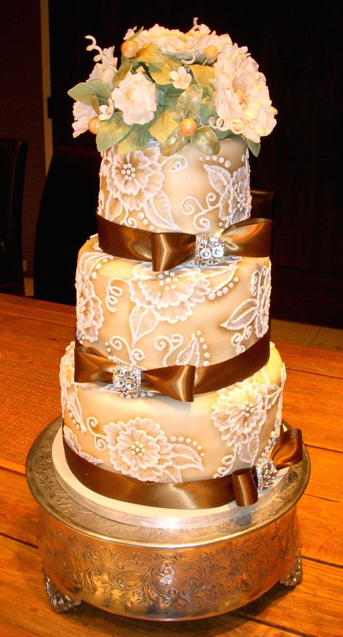 3 tier brown cakes covered with fondant & brown ribbons