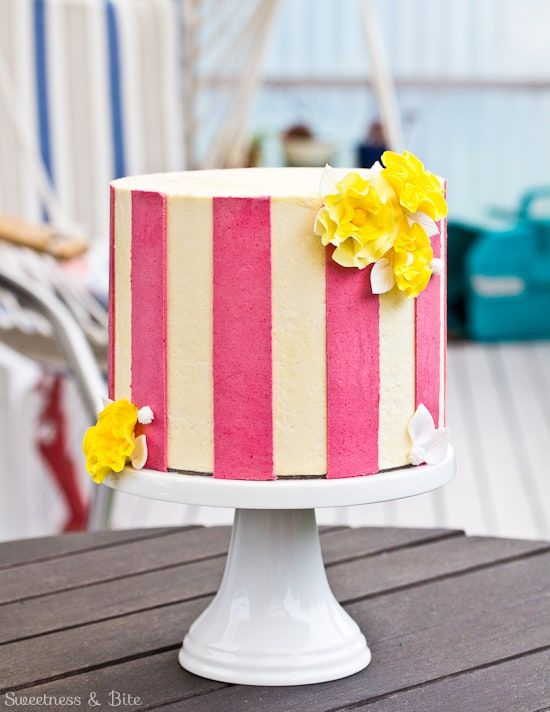 vertical pink and white stripes on cakes with a yellow flower on it