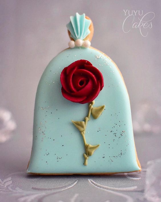 a blue cookie with a red rose on it - Disney Theme Cookie Tutorials