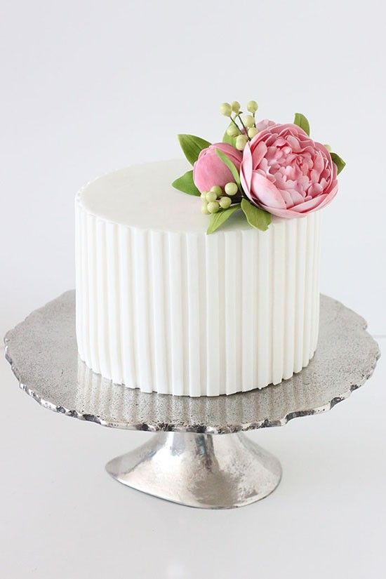 a simple white colored origami skill on cakes with simple sugar flower peony in pink