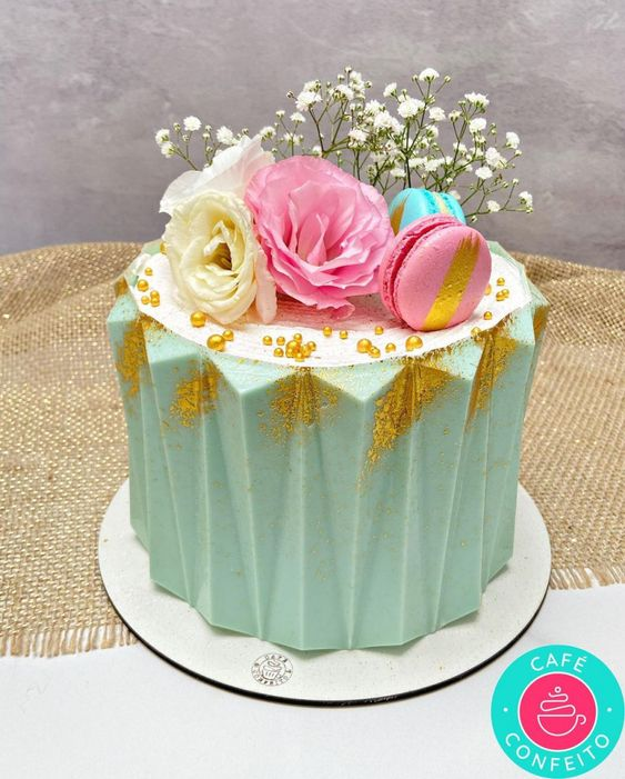 blue colored buttercream with gold work and flower macarons placed on it