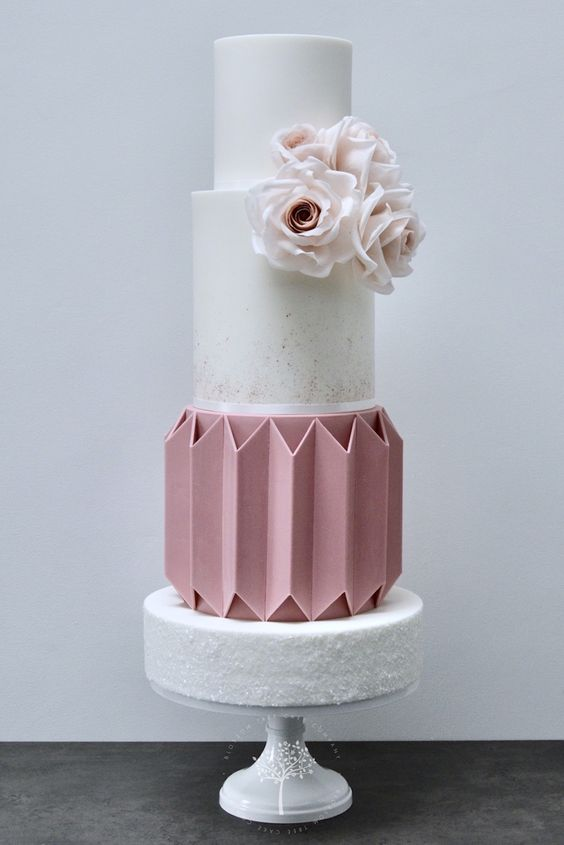 a three tier white and brown colored ganache technique with sugar roses on it