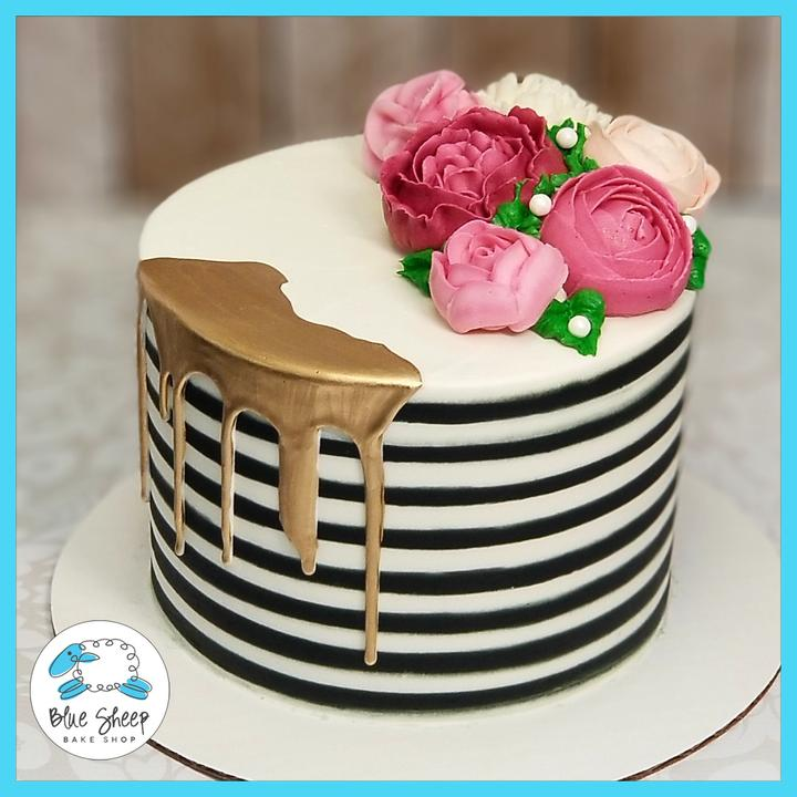 black and white stripe cake with gold drip on it and buttercream flowers