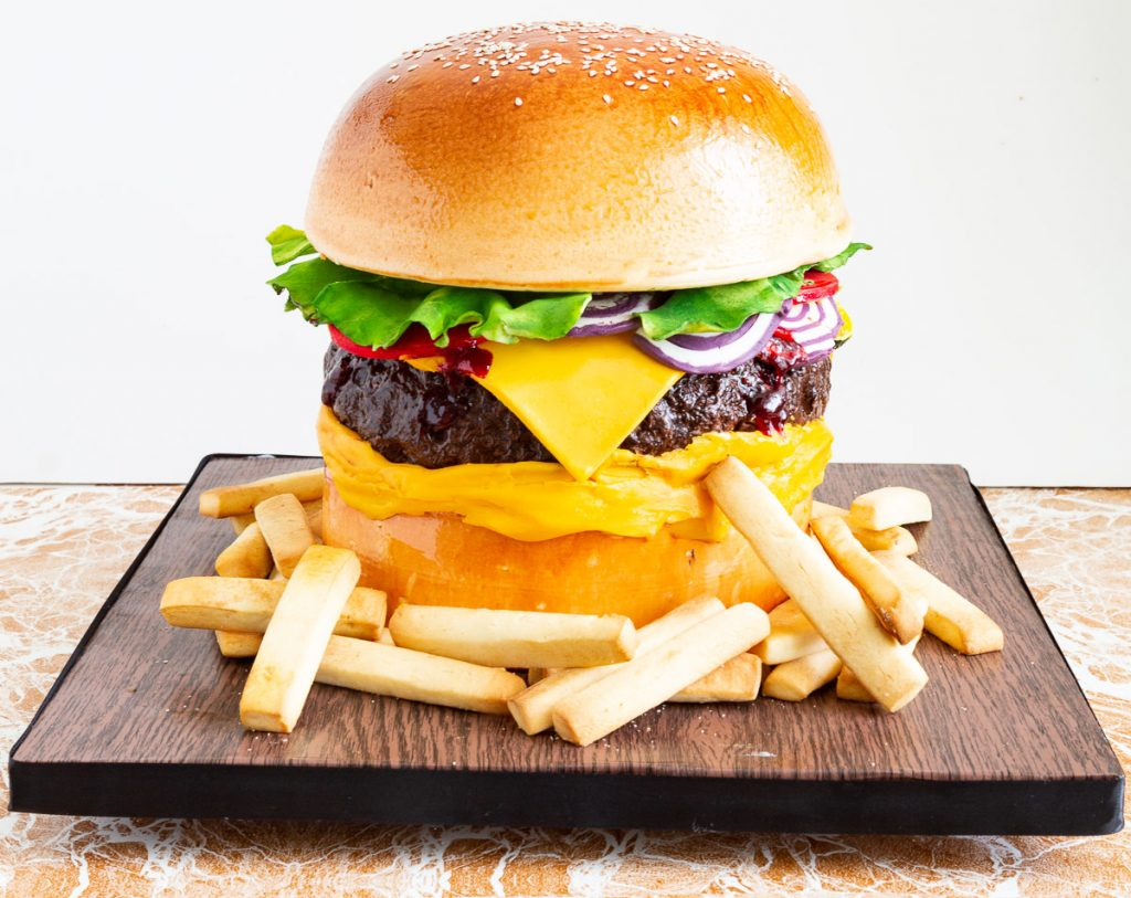 A burger cake on a square wooden cake board.