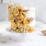 baked orange slices around a butter cream cake with tiny flowers in white - Easy Naked Cake Tutorials