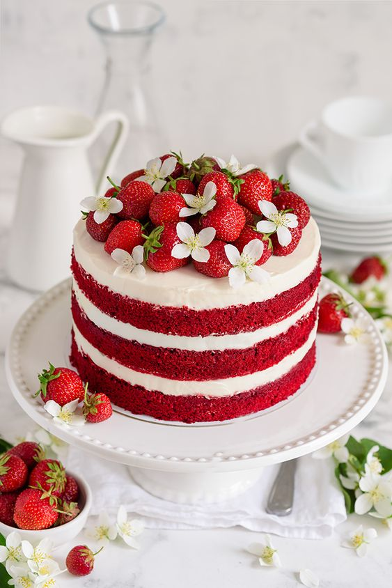 a red and white layer with flowers and strawberries over it