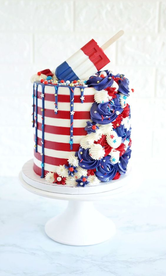 red and blue cake with popsicle on it and buttercream rosettes