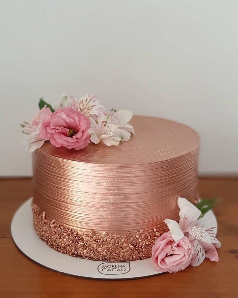 bronse glitter cakes with pink flowers on it