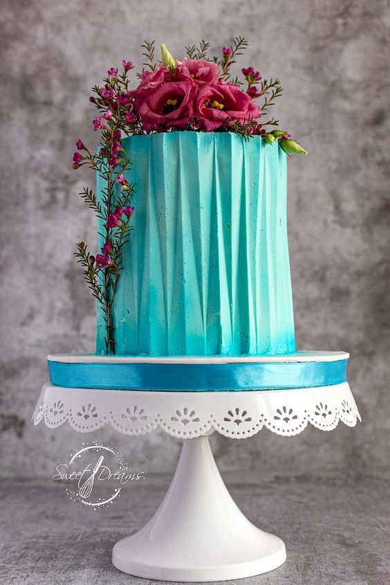blue color colored ganache with pink sugar flowers and leaves