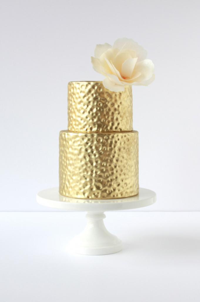 gold fondant covered shimmer cake with a paper flower on it