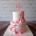 a cross in pink and white on a two tier fondant covered cake with flowers and sugar bow