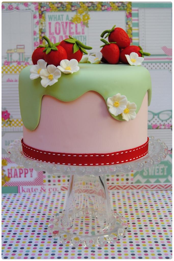 a pink fondant and green effect cake with sugar strawberries