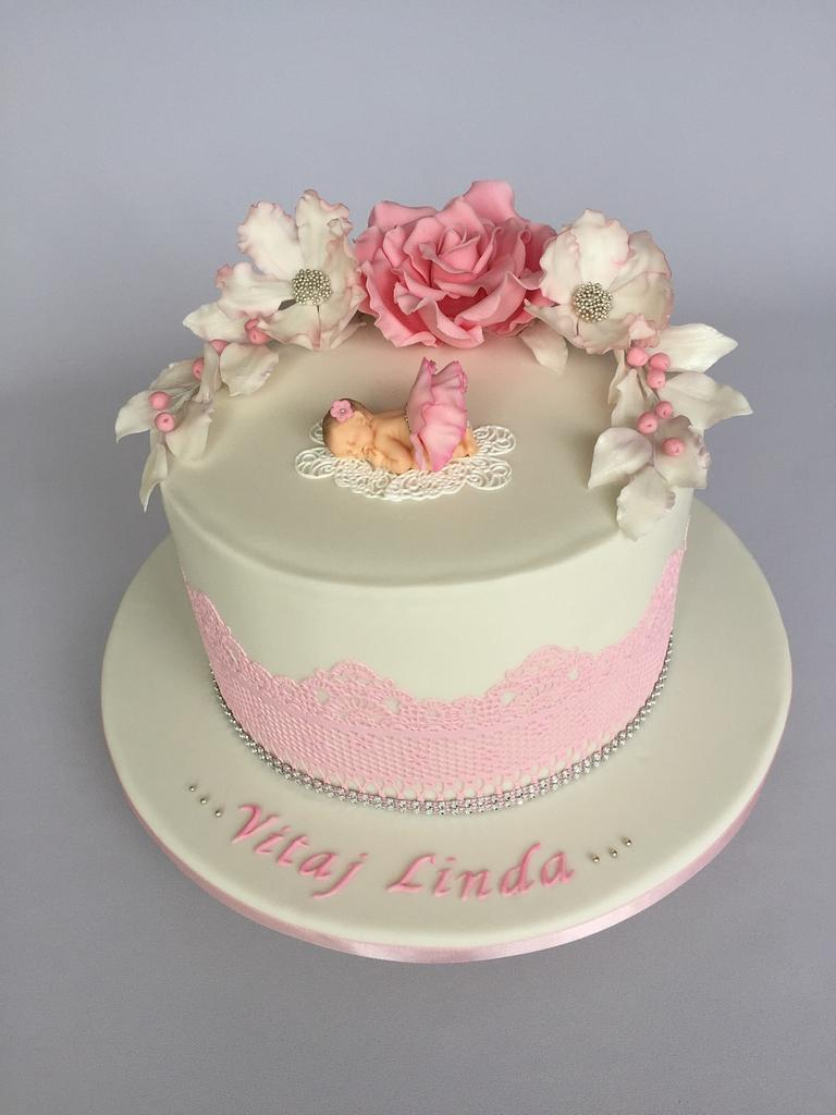 pink rose on a white fondant covered cakes with sugar baby on it