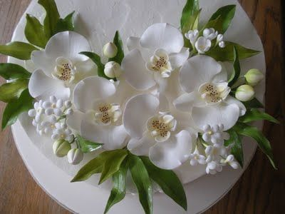 orchids on a white cake with sugar leaves
