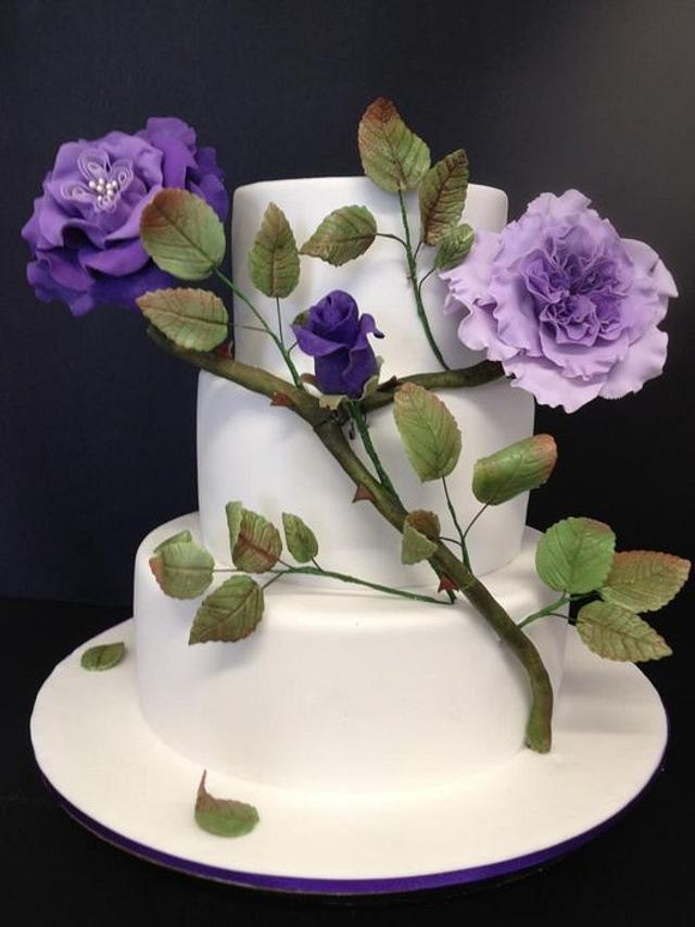 white two tier cake with green branch and purple flowers