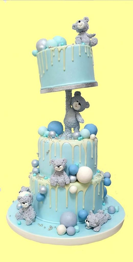 gravity cakes with a fondant figurine carrying another teddy