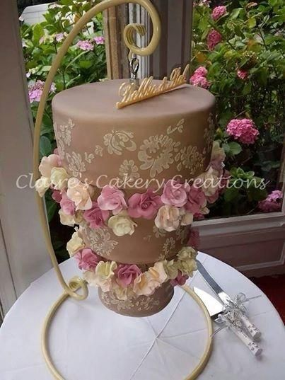 brown cake with royal icing stencil work and sugar flowers