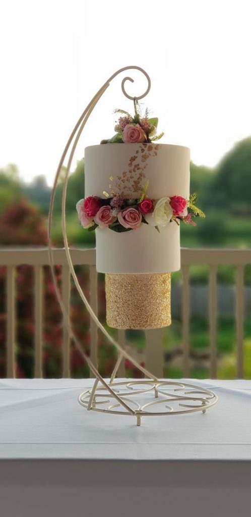 gold and white fondant cake with fresh roses on it