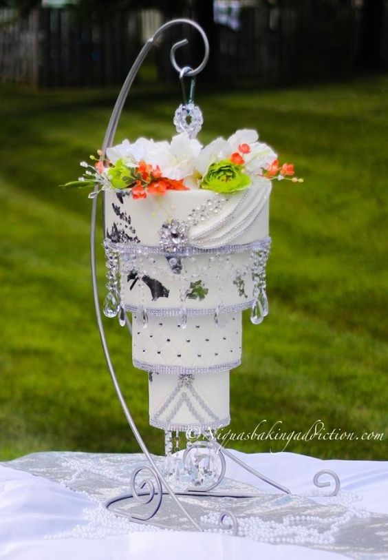 white hanging cake with sugar flowers