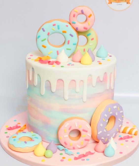 colorful pastel effect donuts on a drip effect cake