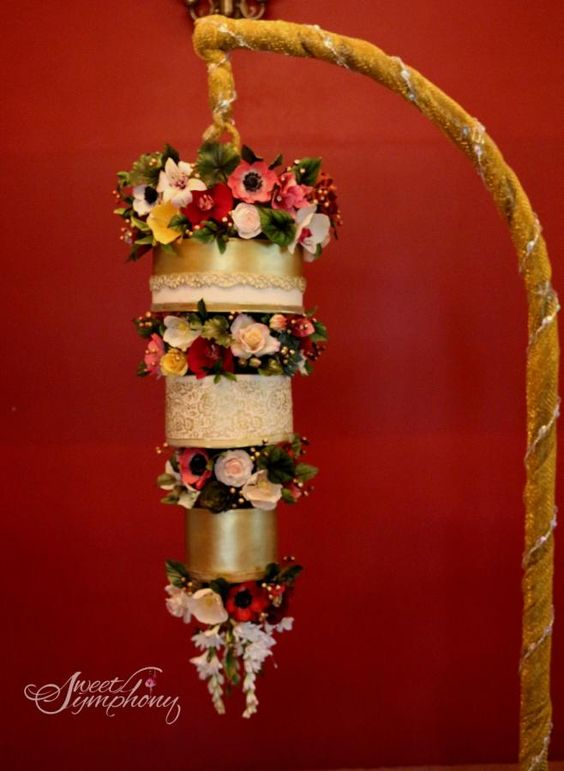 gold and white wedding cake with sugar flowers on it